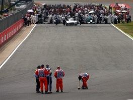 Pořadatelé uklízejí trať po havárii Kimiho Räikkönena ve Velké ceně Británie.