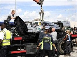 Porouchaný monopost Nika Rosberga odváží technici z okruhu Silverstone.