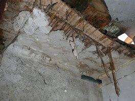 Prohnilý odřezaný trám a zničený původní rákosový strop v komoře.