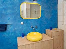 Modrá stěna silně kontrastuje se žlutým umyvadlem.