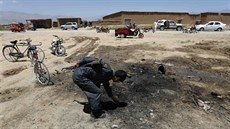 Afghánský policista prohlí�í místo sebevra�edného útoku, kde zahynuli �ty�i...