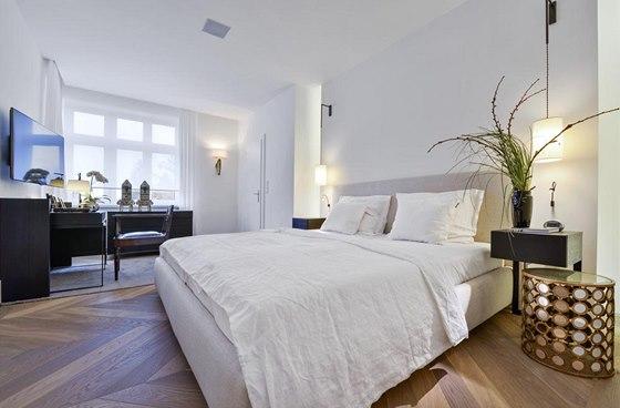 Ložnice je vybavená čalouněným dvojlůžkem (Poliform). Zdobné zlaté noční stolky