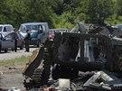 Lidé čekají ve svých autech na cestě do Slavjansku, v popředí je zničené ruské...