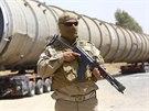 Člen kurdských milic stráží nadměrný převoz mířící do rafinerie na předměstí...
