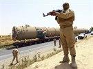 Příslušníci kurdských milic stráží převoz nadměrného nákladu mířícího do...