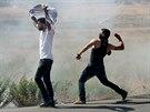Mladí Palestinci ze Západního břehu házejí kameny na policisty během...