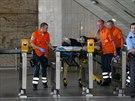 Záchranáři odvážejí zraněného po útoku v metru Kačerov