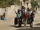 Palestinci, kterří opustili svůj dům na severu města Beit Lahiya, jedou na voze...