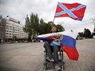 Muž drží vlajku Ruska a Novoruska při demonstraci na Leninově náměstí v centru...