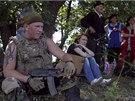 Ukrajinský voják doprovází skupinu obyvatel, která odchází z východoukrajinské