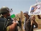 Palestinští demonstranti drží fotografie obětí izraelských náletů a dohadují se