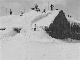 Lyžaři na střeše zasněžené Luční boudy kolem roku 1925 (pohlednice).
