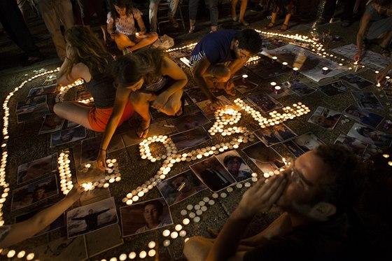 """Izraelští aktivisté ze svíček tvoří nápis """"Promiňte"""" v arabštině. Kolem nápisu"""