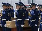 Česná stráž vedle rakví s ostatky obětí zřícení malajsijského letadla na...