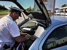 Policista zapisuje do notebooku �daje o �idi�i p�i kontrole kamion�. Speci�ln�...