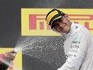 TO JE ZA NIKA. Lewis Hamilton schytává sprškou sektu na stupních vítězů v...