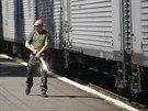 Ozbrojen� prorusk� separatista hl�dkuje u vlaku, ve kter�m jsou ulo�eny ostatky...