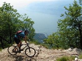 Kamenitá cesta, za ní příkrá sráz a v dáli jezero. Tradiční scenérie z výletu...