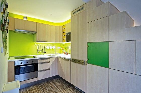 Zelená dvířka rozbíjí monolitickou celistvost úložných skříněk pod schodištěm.