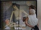 Turisté si prohlíží malbu znázorňující mučeného zajatce Rudých Khmérů. Muzeum