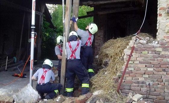 Hasiči stabilizují zřícený strop ve stodole v Olešnici u Chlumce nad Cidlinou....