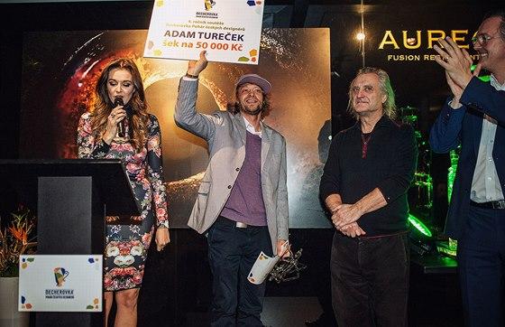 Adam Tureček přebírá šek s výhrou a skleněný pohár za vítězství v soutěži.