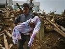 Mu� nese t�lo sv�ho mrtv�ho syna pot�, co bylo nalezeno pod troskami jejich...