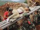 Zraněná žena je snášená záchranáři po zemětřesení v Číně (4. srpna 2014).