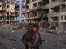 Žena se svou dcerou se dívají na zničené domy v Pásmu Gazy (7. srpna 2014).