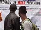 Plakát o prevenci eboly v Libérii si čtou dva muži (8. srpna 2014).