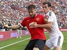 Alexander Buttner (vlevo) z Manchesteru United si kryje míč před Garethem Balem...