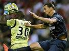 Johny Placide (vlevo) z Remeše zasahuje před Zlatanem Ibrahimovicem z Paris St....