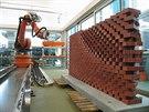 Průmyslový robot staví jednotlivé cihly na sebe přesně podle předem...