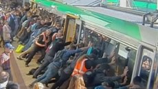 Cestující naklán�jí vlak v západoaustralském m�st� Perth, aby pomohli mu�i,...