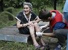 Zdravotník ošetřuje ženu zraněnou při bojích mezi ukrajinskými vládními silami...