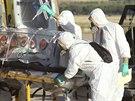 Zdravotníci ve speciálních oblecích převážejí španělského misionáře Miguela...