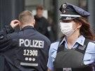 Němečtí policisté v ochranných rouškách stojí před uzavřeným úřadem práce v...
