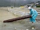 Muž odklízí naplavené dřevo z ulice města Shingu, které zaplavila řeka...