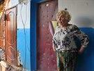 Raisa Jelisjevová stojí ve svém domě zničeném dělostřeleckým granátem.
