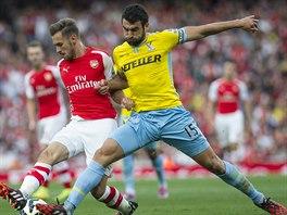 Souboj o míč v podání Aarona Ramseyho (vlevo) z Arsenalu a Mileho Jedinaka z...