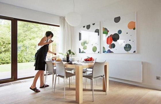 Na míru vyrobený masivní dubový stůl doplňují subtilní designové židle v