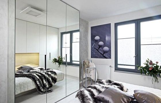 Naproti lůžku je další zrcadlová šatní skříň, která pomáhá místnost opticky