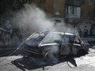 Obyvatelé Doněcku obhlížejí automobil zničený údajně ukrajinskou dělostřelbou...