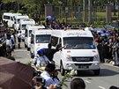 Bílé vozy odvezly rakve s obětmi letu MH17 z letiště (22. srpna 2014).