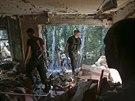 Proru�t� ozbrojenci proch�zej� domem poni�en�m ost�elov�n�m (23. srpna 2014).