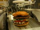 """Hamburger sestavený """"jako"""" na běžícím pásu."""