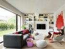 Obývací pokoj je zařízený v neutrálních barvách. Pohodlná tmavě šedá pohovka je