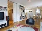 Hlavní obývací prostor oddělují od předsíně posuvné velkoformátové dveře, které se zasouvají za novou vestavěnou knihovnu.