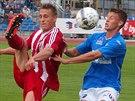 Třinecký Petr Lisický (v červeném) odkopává míč před Michalem Pavlatou z Ústí...
