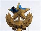 Horolezec přebarvuje vrcholek věže stalinského mrakodrapu. Ráno 20. srpna...